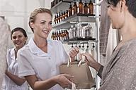 Shop assistant in wellness shop handing over bag to client - ZEF006518