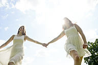 Two happy young women hand in hand - BFRF001262