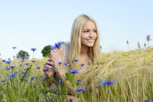 Smiling young woman crouching in a field - BFRF001253