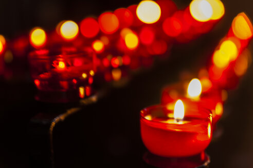 Lighted votive candles in a church - TCF004709