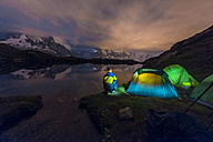 France, Mont Blanc, Lake Cheserys, backpacker and tents on the shore of the lake by night - LOMF000023