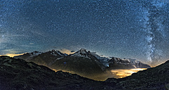 France, Mont Blanc, Lake Cheserys, Milky way and Mount Blanc by night with the valley lighted by the lights of the town of Chamonix - LOMF000007