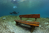 Austria, Styria, Tragoess, lake Gruener See, diver and flooded park bench - YRF000086
