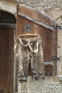 Germany, Bavaria, short leather trousers hanging on shutter for sale - OPF000058