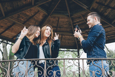 Spain, Barcelona, young man taking a photo of his two female friends - GEMF000249
