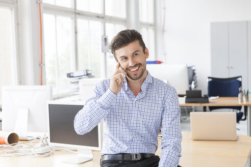 Portrait of smiling businessman telephoning in an office - JUNF000324