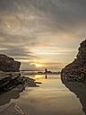 Spain, Galicia, Ribadeo, Playa de Aguas Santas at sunset, small person on the beach - LAF001408