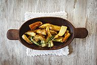 Wooden bowl of potato wedges with rosemary - EVGF001827