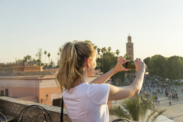 Morocco, Marrakesh, young female tourist taking a picture with her smartphone - JUNF000347