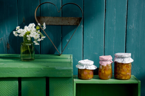 Three glasses of homemade rhubarb apricot jam, heart-shaped cutter and blossoming woodruff - GIS000125