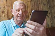 Portrait of senior man using phablet - TAM000059