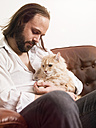 Maine Coon in the arms of snoozing man - TAM000176