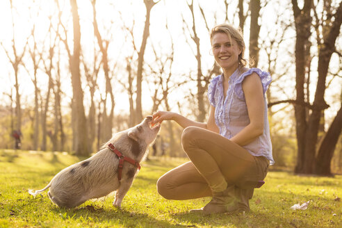 Smiling woman with piglet in park - TAM000192