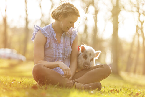 Smiling woman sitting with piglet in park - TAM000196