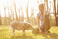 Smiling woman sitting with piglet in park - TAM000200