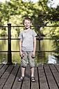 Portrait of little boy standing on footbridge in a park - TAM000112