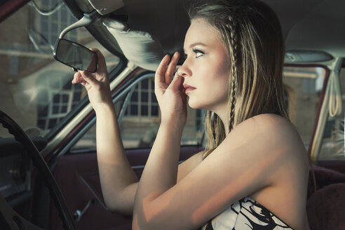 Young woman checking her make up in rear-view mirror of vintage car - TAM000203