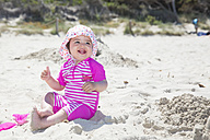 Spain, Majorca, smiling baby girl sitting on the beach - ROMF000062