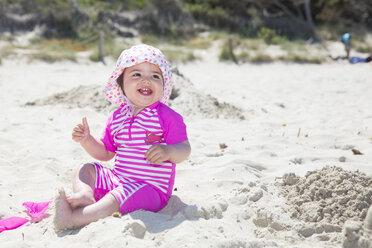 Spain, Majorca, smiling baby girl sitting on the beach - ROMF000062