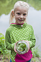 Germany, Girl holding glass with caterpillar of peacock butterfly - MJF001556