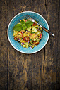 Bowl of couscous salad on wood - LVF003599