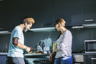 Young man preparing food in the kitchen while woman watching him - EBSF000709