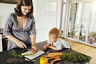 Pregnant woman cutting vegetables with her son in the kitchen - MFF001764