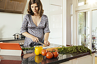 Pregnant woman cutting vegetables in her kitchen while looking at digital tablet - MFF001765