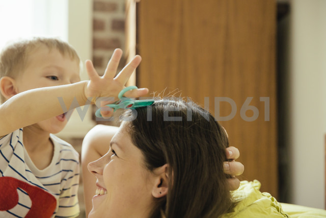 Little boy pretending to cut mother's hair at home - MFF001772