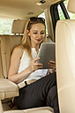 Blond woman sitting on back seat of a car using digital tablet - JUNF000371