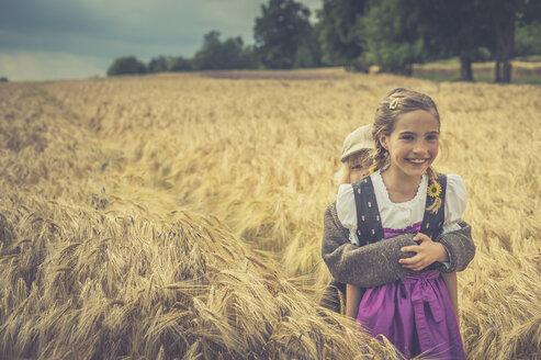 Germany, Saxony, two children standing in a grain field - MJF001577