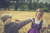 Germany, Saxony, two children playing in a grain field - MJF001579