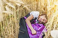 Germany, Saxony, portrait of smiling girl lying in a grain field wearing dirndl - MJF001580