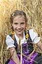 Germany, Saxony, portrait of smiling girl sitting in a field wearing dirndl - MJF001583