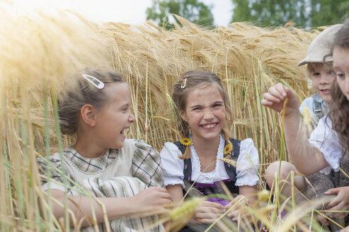 Germany, Saxony, children sitting in a grain field having fun - MJF001584