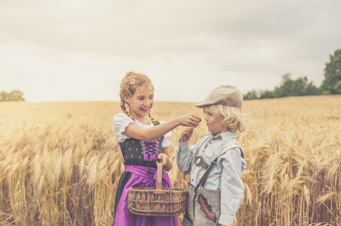 Germany, Saxony, two children standing in front of a grain field - MJF001586