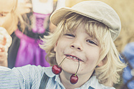 Portrait of little boy holding two cherries with his mouth - MJF001587