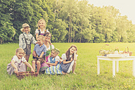 Germany, Saxony, group picture of children in traditonal clothes and their educator on a meadow - MJF001627