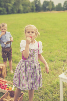 Germany, Saxony, portrait of girl wearing dirndl eating a red radish - MJF001622