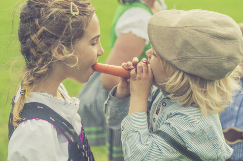 Germany, Saxony, boy and girl together biting off a carrot - MJF001624