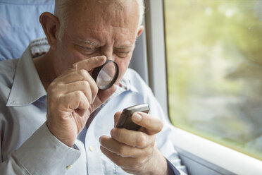 Senior man reading text on a cell phone with a magnifying glass - TAMF000123