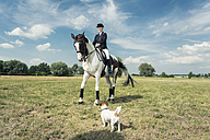 Dressage rider on horse with little dog standing in the foreground - TAMF000234