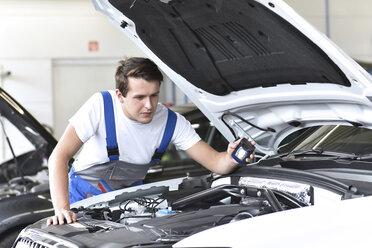 Mechanic examining engine of a car in a garage - LYF000428