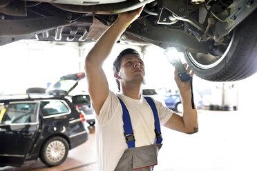 Mechanic examining underbody of a car in a garage - LYF000447