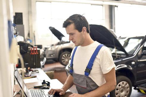 Car mechanic using laptop in a garage - LYF000436