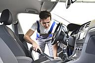 Man hoovering car interior - LYF000451