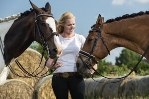 Germany, Wiesenau, blond woman with two horses - TAM000245