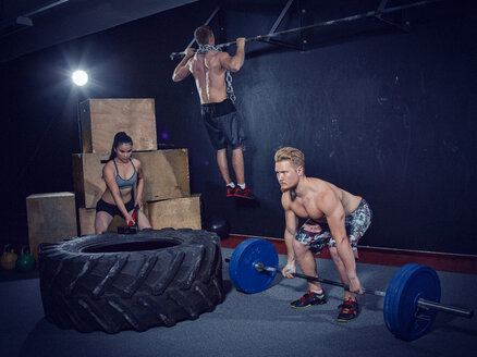 Three CrossFit athletes at workout - MADF000322
