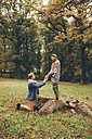 Young man kneeling down and proposing to his girlfriend in an autumnal park - CHAF000201