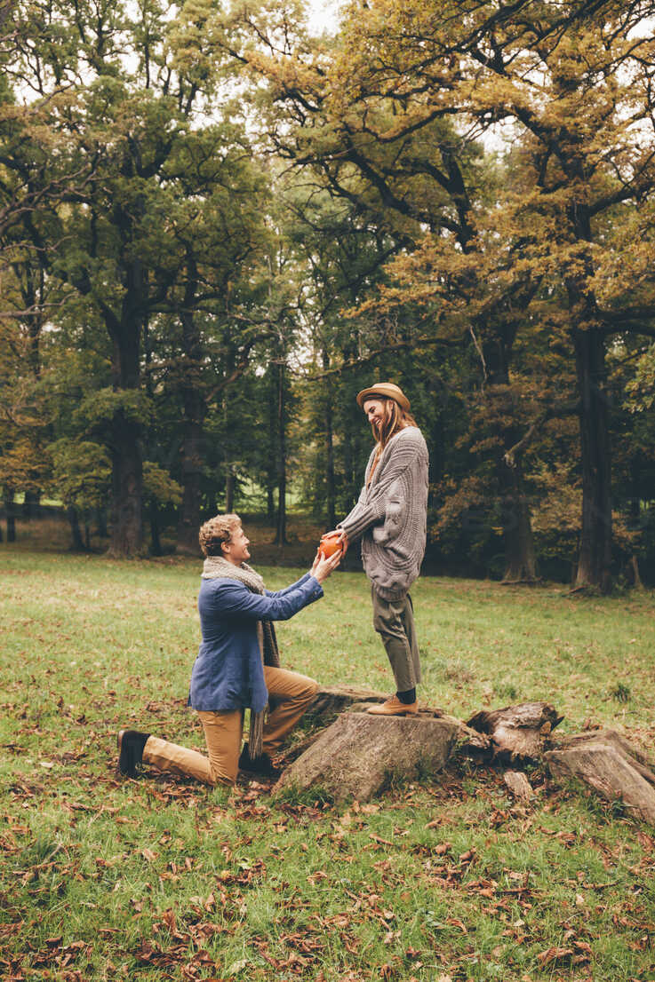 Young man kneeling down and proposing to his girlfriend in an autumnal park - CHAF000201 - Chris Adams/Westend61